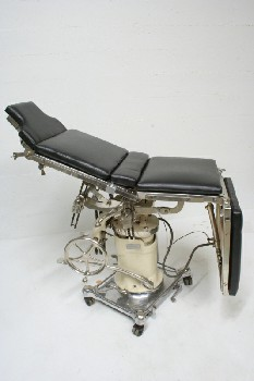 Chair, Medical, OPERATING,ADJUSTING LEVERS,WHITE CENTER COLUMN, BLK PADDING,ROLLING, STAINLESS STEEL, SILVER